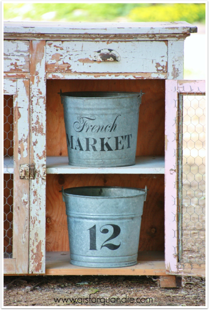 stenciled buckets in cupboard