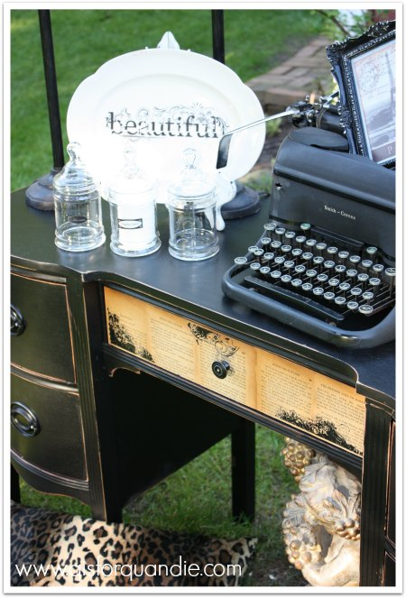 Black desk with decoupaged book pages